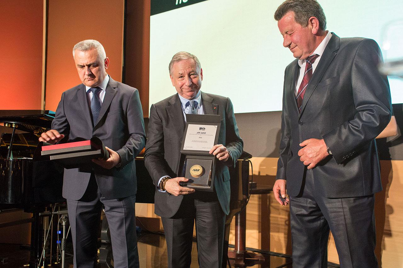 Predsjednik FIA-e g. Jean Todt pokazuje uručeno priznanje HAK-a FIA-i, uz njega predsjednik HAK-a Slavko Tušek (na slici desno) i zamjenik predsjednika HAK-a Ivo Bikić (na slici lijevo)